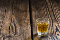 Small whiskey shot on an old wooden table Royalty Free Stock Images