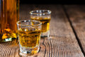 Small whiskey shot on an old wooden table Royalty Free Stock Photos