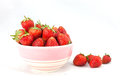 Small white bowl filled with red strawberries succulent juicy fresh ripe isolated on Royalty Free Stock Photo
