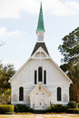 Small white church with green steeple a wooden down sidewalk under nice sky Royalty Free Stock Photo
