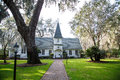 Small white church past brick walk and gas lamp a under oak trees draped with spanish moss Stock Photos