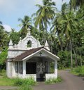 Small white goan church a on a tiny village road lined with palm trees Stock Photo