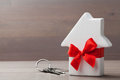 Small white house tied red ribbon and bunch of keys on wooden background. Gift, real estate purchase or buying a new home concept. Royalty Free Stock Photo
