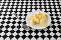 Plate of pineapple slices with a fork on a tablecloth Royalty Free Stock Photo