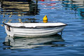 Small white skiff with reflections in calm water at the harbour Royalty Free Stock Images