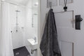 Small white tiled ensuite bathroom with shower and hanging towel Royalty Free Stock Photo