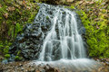 Small wide waterfall with mossy rocks and smooth water Royalty Free Stock Photo