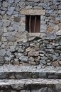 Small window on stone wall Royalty Free Stock Photo