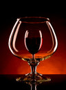 Small wineglass is visible through a large glass of wine image on dark orange background Royalty Free Stock Image