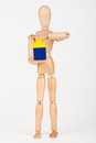 Small wood mannequin holding colourful blocks