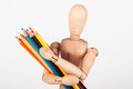 Small wood mannequin standing with pencils