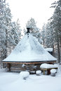 Small wooden blockhouse with pyramid shape roof in winter in the white snow in the snowy forest of pine trees Royalty Free Stock Photography