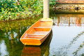 Small wooden boat on garden pond Royalty Free Stock Photo