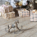 Small wooden rocking horse under Christmas tree with gifts Royalty Free Stock Photo