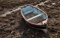 Small wooden rowboat moored at low tide Royalty Free Stock Photo