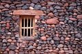 Small wooden window in an ancient stone wall Royalty Free Stock Photo