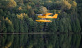 Small yellow airplane on pontoons comes in for a landing on a calm lake single engine an eastern ontario summer x s evening Stock Photo