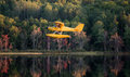 Small yellow airplane on pontoons comes in for a landing on a calm lake single engine an eastern ontario summer x s evening Royalty Free Stock Photos