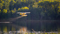 Small yellow airplane on pontoons takes off from a lake an eastern ontario summer x s evening Stock Photo