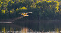 Small yellow airplane on pontoons takes off from a lake an eastern ontario summer x s evening Royalty Free Stock Images