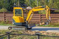 Small yellow crawler excavator for screwing piles on road Royalty Free Stock Image