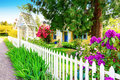 Small Yellow house exterior with White picket fence Royalty Free Stock Photo