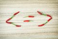 Smaller than greater than and equal sign of chilli peppers on the wooden background Royalty Free Stock Photo