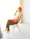 Smart Asian woman sitting and holding red vintage phone Royalty Free Stock Photo