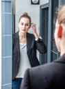 Smart beautiful young woman looking at her reflection in mirror Royalty Free Stock Photo