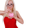 Smart blonde young woman saving money in piggy bank isolated Royalty Free Stock Photography