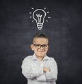 Smart boy with solution idea lightbulb above head Royalty Free Stock Photo
