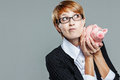 Smart business woman questioning her piggy bank isolated on grey Royalty Free Stock Photos