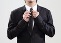 Smart businessman adjust his tie before start with job background Stock Photo