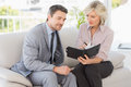 Smart businessman and his secretary looking at diary on sofa home Royalty Free Stock Images