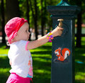 Smart cute girl near the tap park outdoor Royalty Free Stock Photography