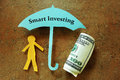 Smart investing paper man under umbrella Royalty Free Stock Images