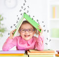 Smart kid in glasses under falling digits happy roof made from book hiding from Royalty Free Stock Photo