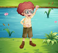 A smart looking boy standing near the river illustration of Stock Photography