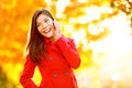 Smart phone autumn woman talking on mobile in fall girl having smartphone conversation sun flare foliage portrait Stock Images