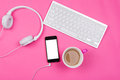 Smart phone coffee headphones and wireless keyboard high angle view of white with isolated white screen in pink cup white on pink Royalty Free Stock Images