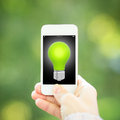 Smart phone light bulb hand against green spring background ecology concept Stock Photography