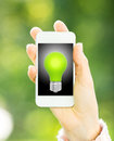 Smart phone light bulb hand against green spring background ecology concept Stock Photos