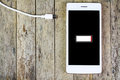 Smart phone need to charge battery on wooden Stock Photography