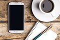 Smart phone with notebook and cup of strong coffee