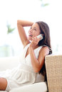 Smart phone pretty woman talking cheerful sitting asian caucasian model in white dress hand on black hair Stock Photos