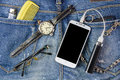 Smart phone, Spectacles, portable battery and watch on jeans bac Royalty Free Stock Photo