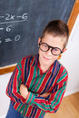 Smart schoolboy at chalkboard eminent wearing glasses standing in front of Stock Photos
