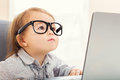 Smart toddler girl wearing big glasses while using her laptop Royalty Free Stock Photo
