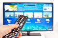 Smart tv and  hand pressing remote control Royalty Free Stock Photo