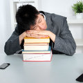 Smart young asian business man student sleeping top pile hardcover books seated table office Royalty Free Stock Photography